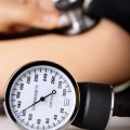 Doctor/nurse checking blood pressure with sphygmomanometer guage in focus.