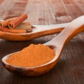 Cinnamon powder on wooden spoon.